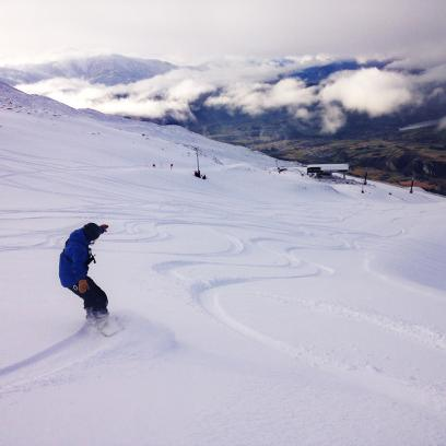 Lone snowboarder enjoying fresh turns at Coronet Peak this morning